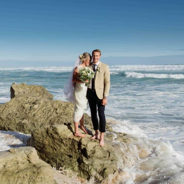 Bride and groom on a rock at Gibson's Steps in Victoria