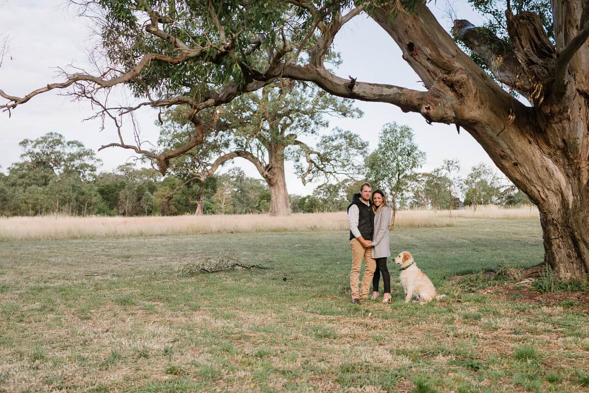Couple with their dog stood under a tree