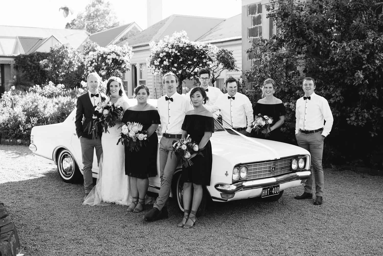 Wedding party leaning on car at Narmbool Sovereign Hill