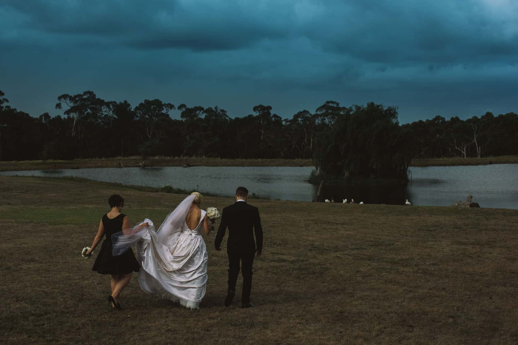 Moody portrait of wedding couple with stormy sky