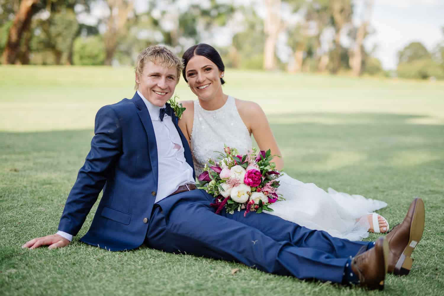 Bride and groom relax on the grass at Colac golf club