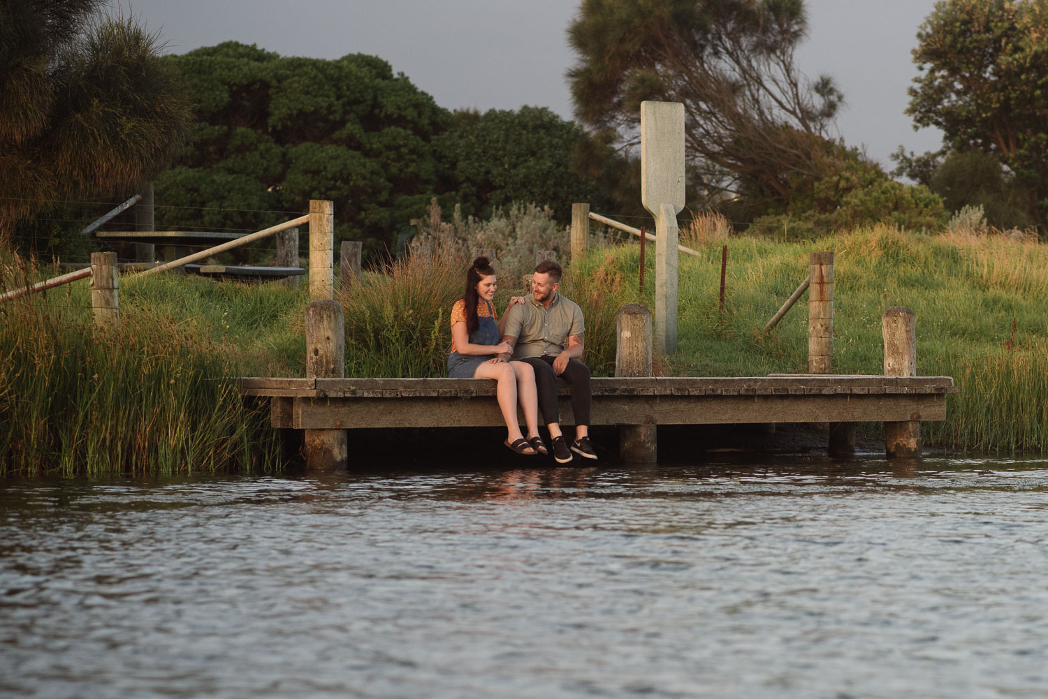 Couple sitting by the water at Apollo bay during their engagement session