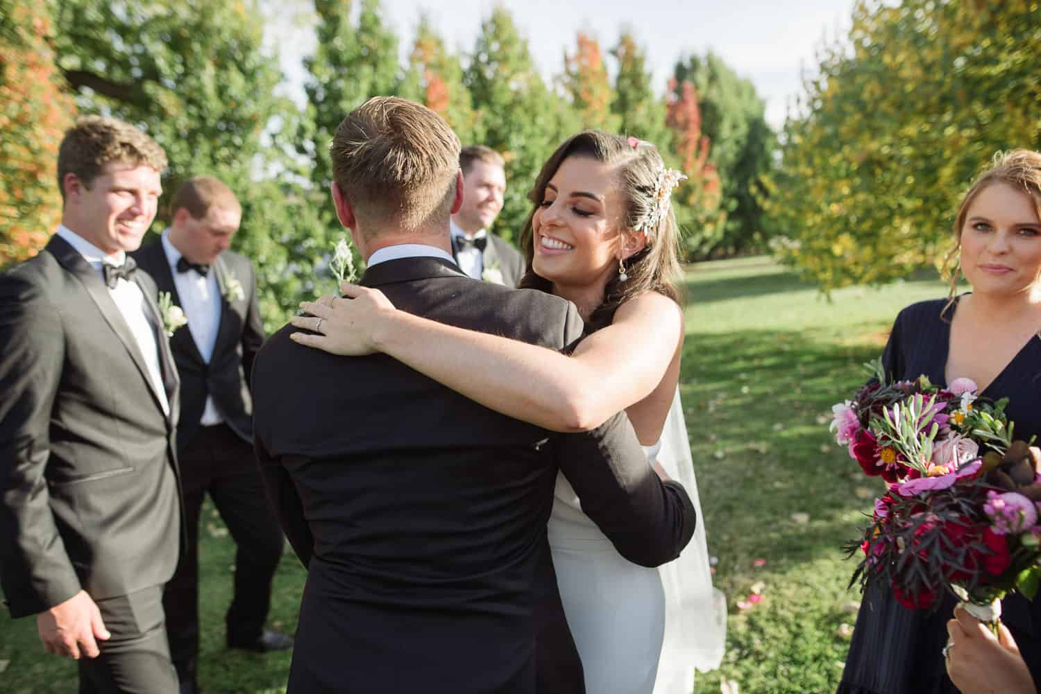 Bride and groom hugging at a backyard wedding