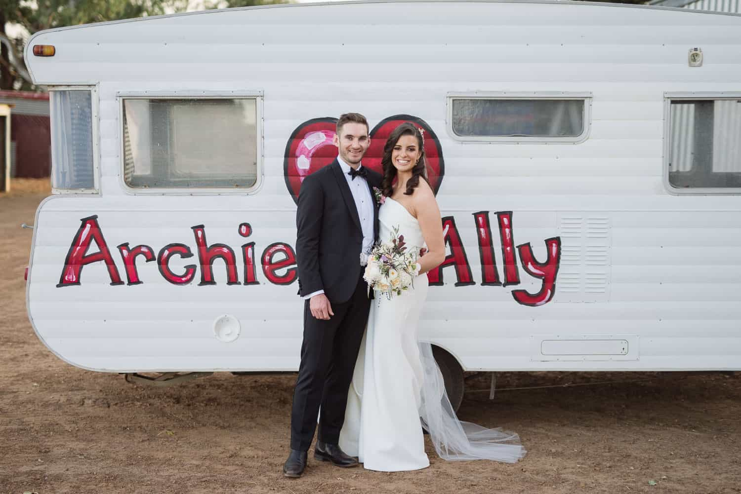Archie and Ally in front of a custom painted caravan