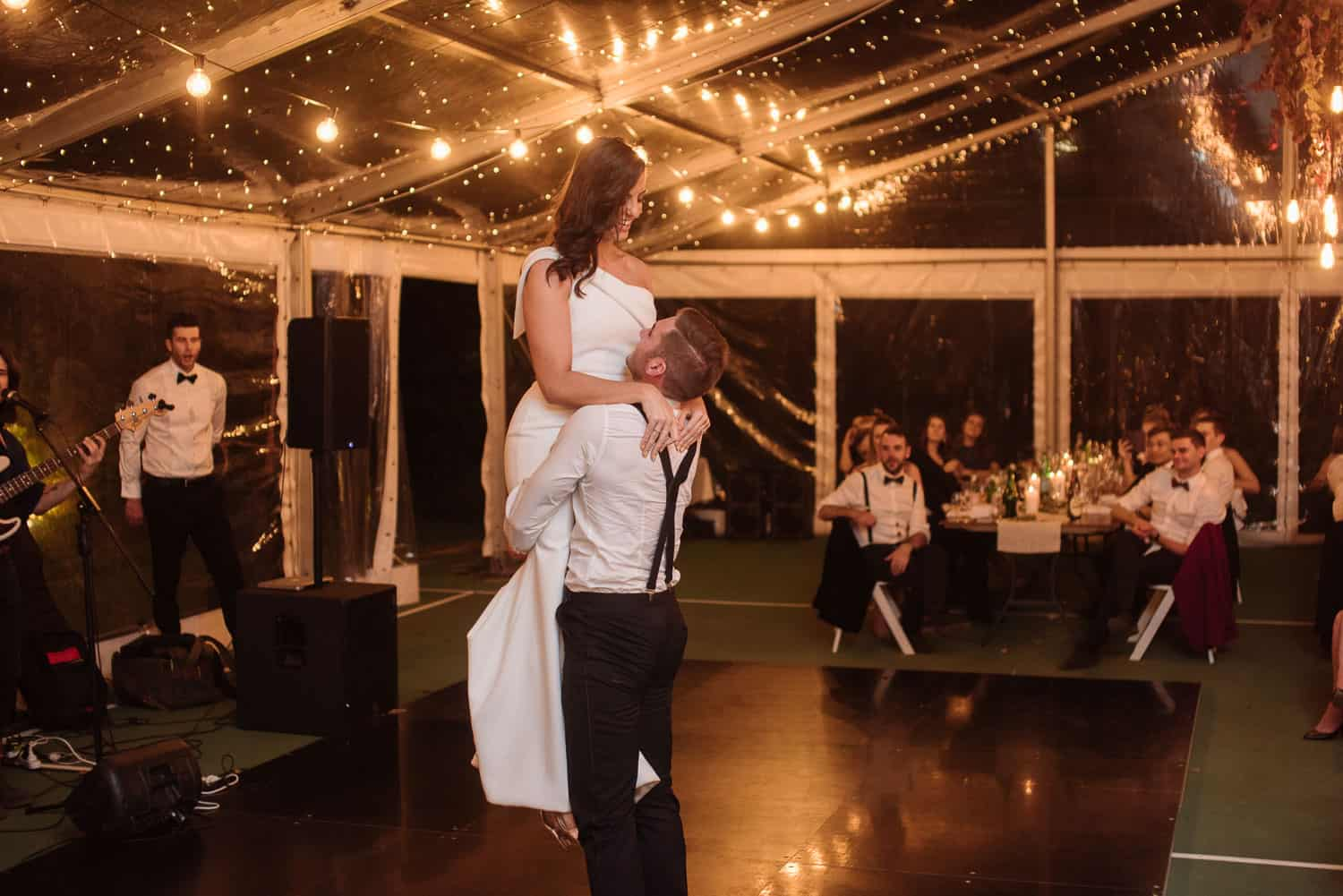 Groom lifts bride during their first dance