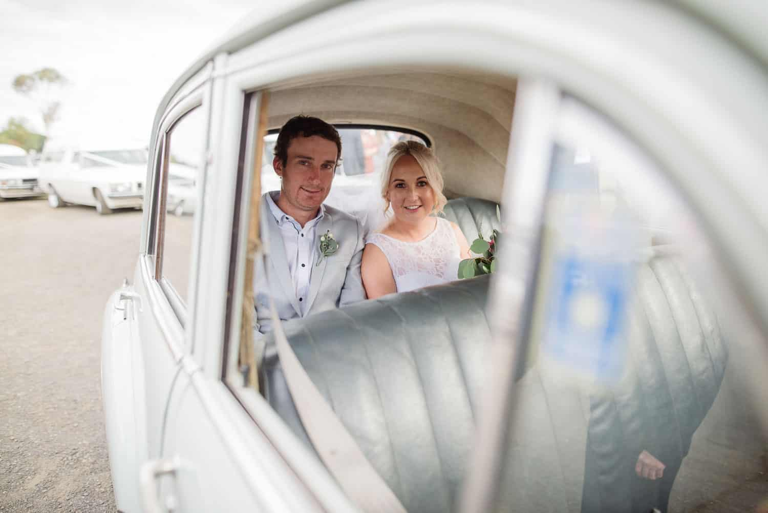 Bride and Groom sitting in their wedding car