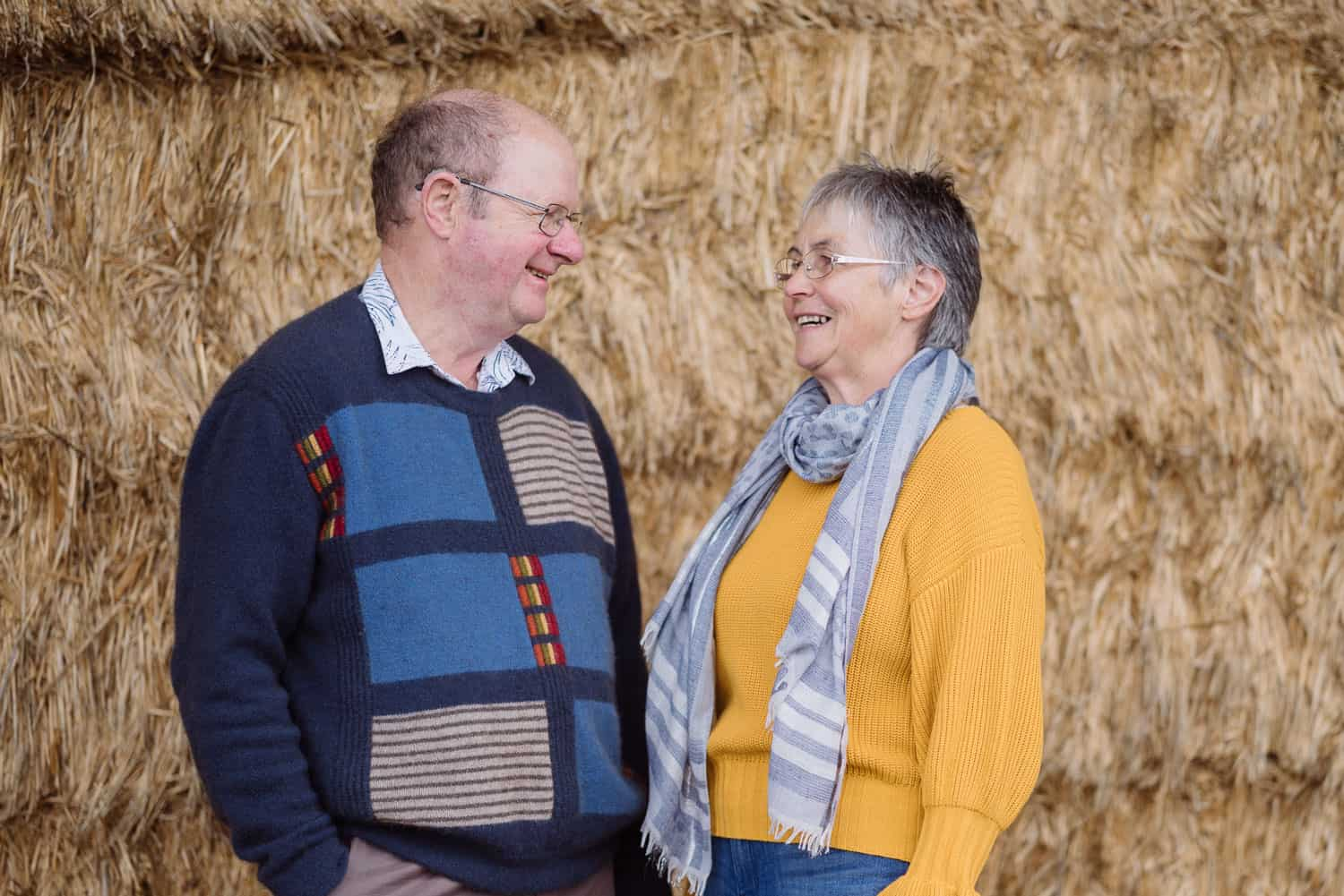 Portrait of an older couple in a hayshed