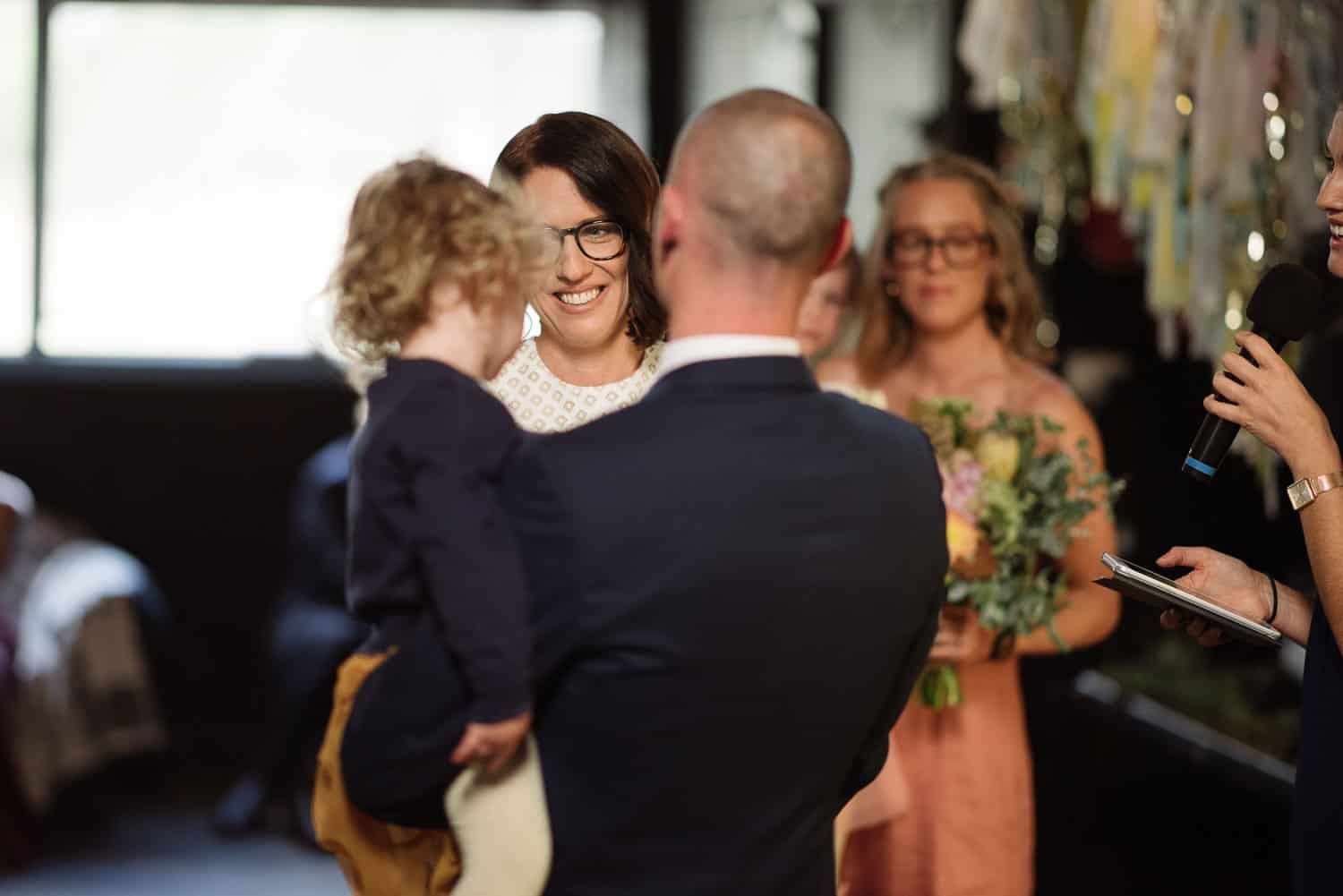 Bride looks at groom and her daughter
