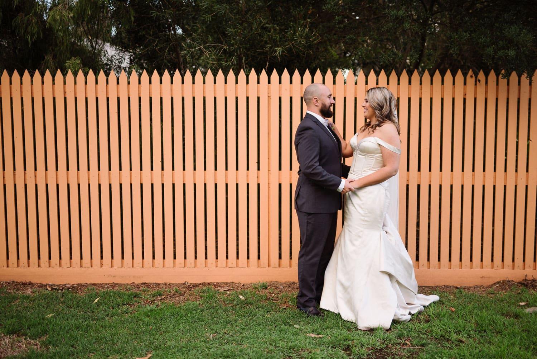 Wedding portrait with an orange fence