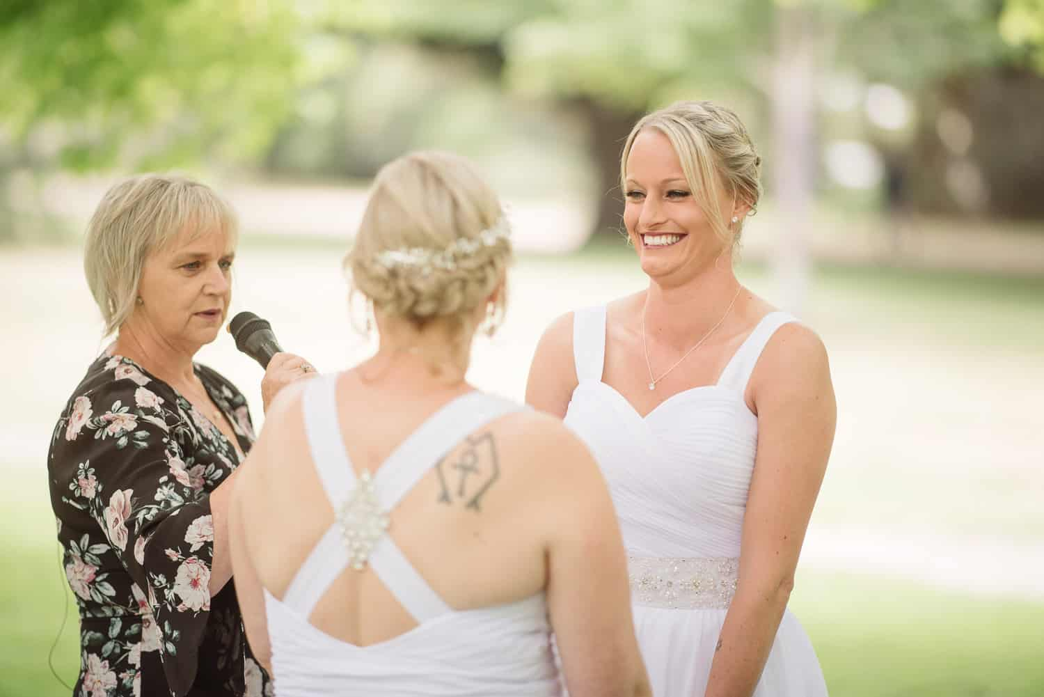 Brides laughing during their wedding ceremony at colac botanic gardens