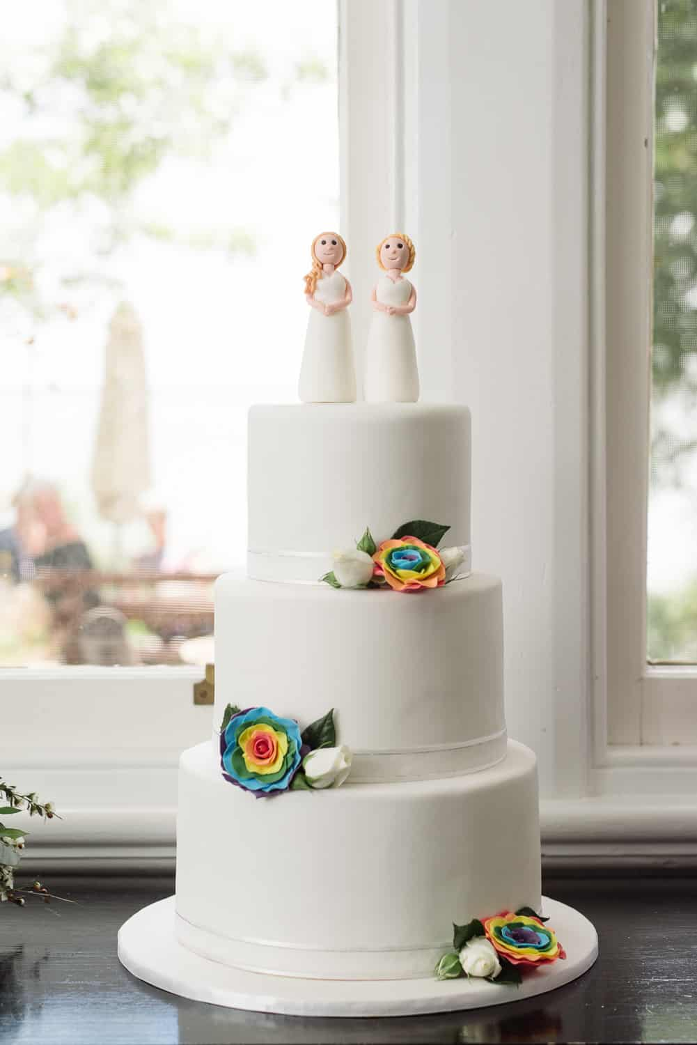 Same sex wedding cake with rainbow flowers