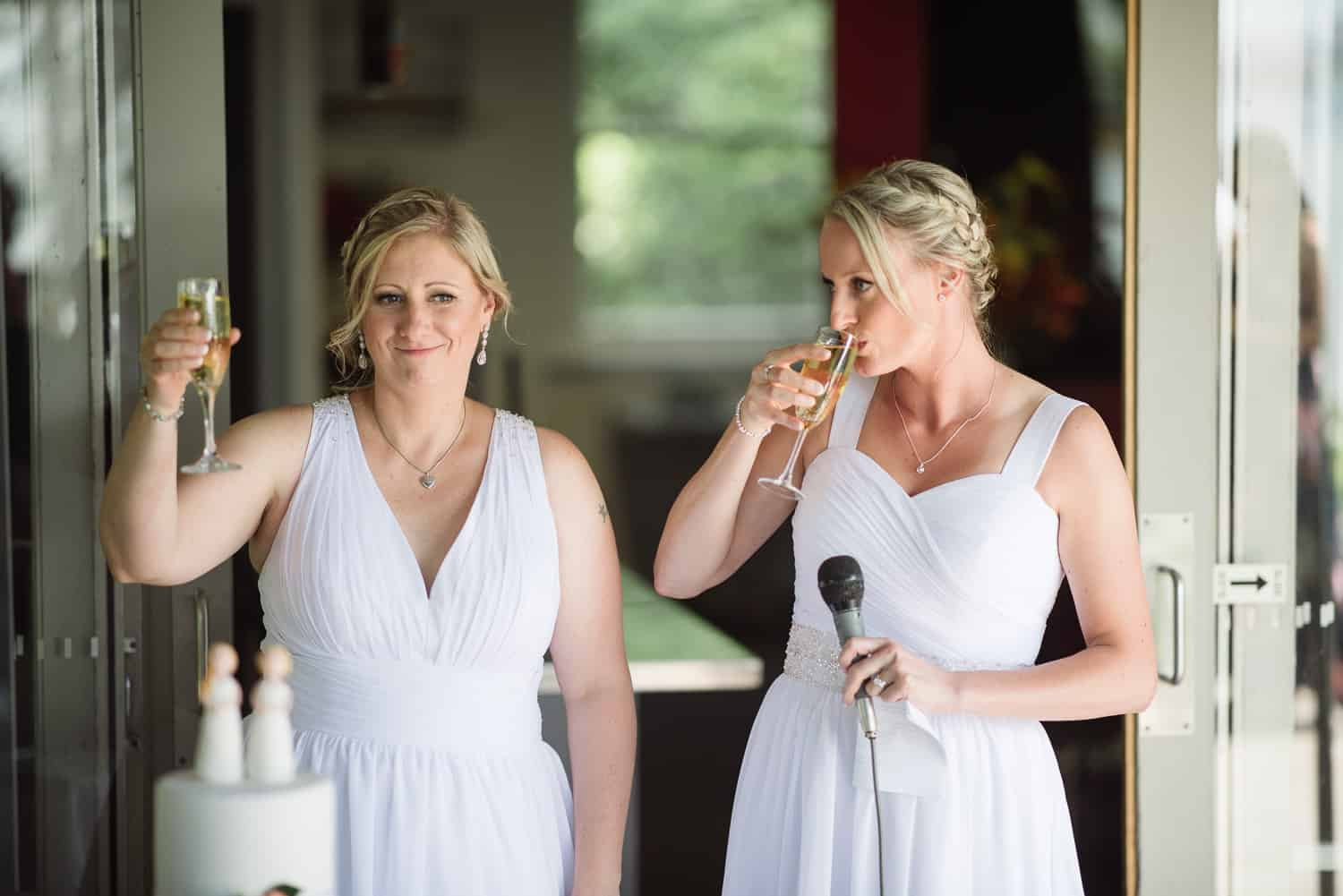 Brides toasting guests at their same sex wedding