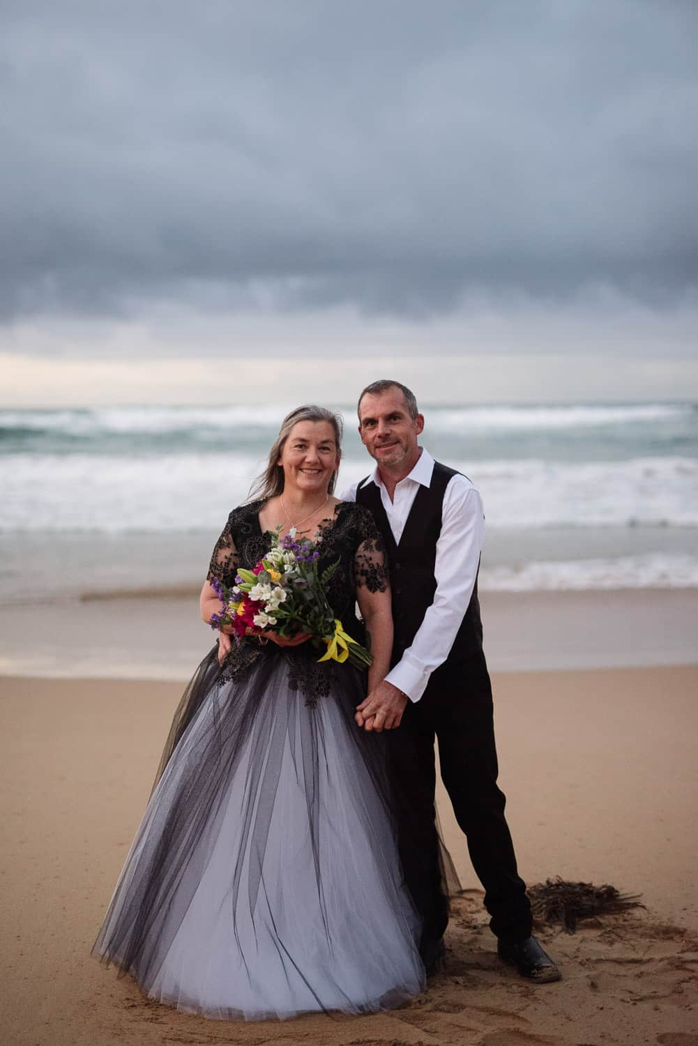 Bride and Groom smiling on the beach
