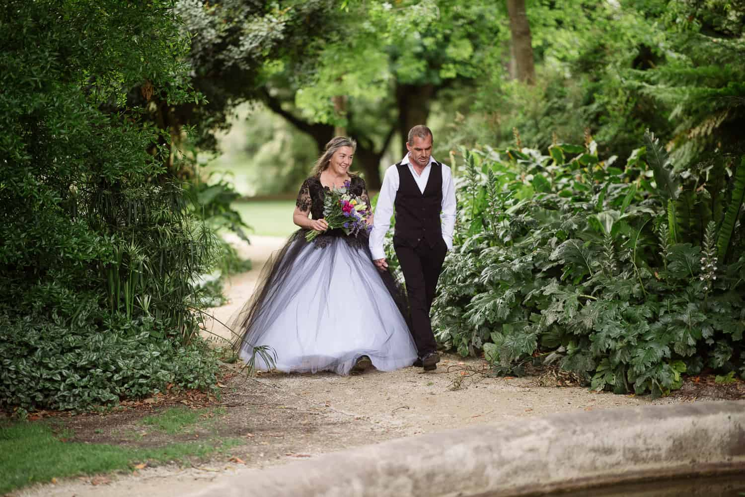 Bec and Ted enetering their wedding in Colac Botanic Gardens
